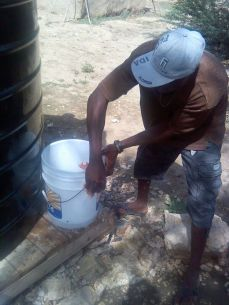 One of our operators cleaning a bucket for a water customer. He is using detergent and bleach to make the bucket safe to transport the clean water.