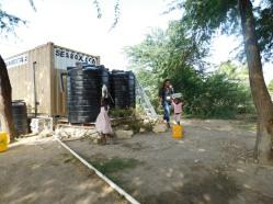 Nadedge helps some children get water.
