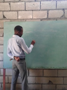 Mr. Eric teaches computer literacy to children in Grande Saline.