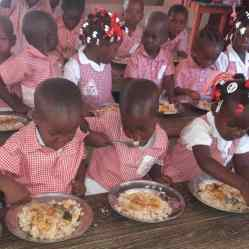 School children enjoy a hot lunch provided in part by proceeds from the community garden.