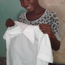 A sewing student shows the blouse she is making.